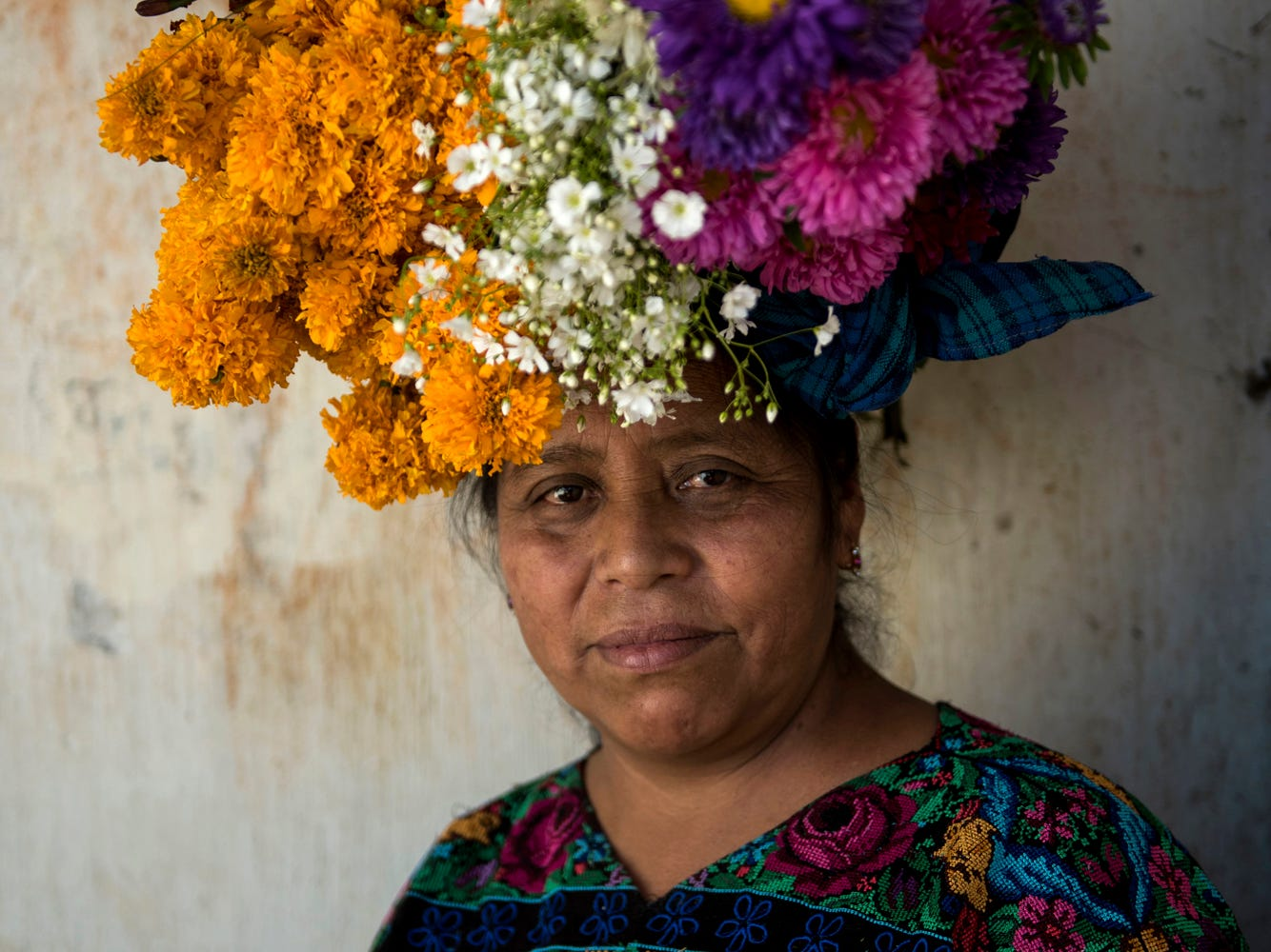 Olga Socorec, 54, balances flowers on her head as she pauses to pose for a portrait while decorating the tombs of family members, including her father's, during Day of the Dead celebrations at the cemetery in Santiago Sacatepequez, Guatemala, Thursday, Nov. 1, 2018. (AP Photo/Oliver de Ros)