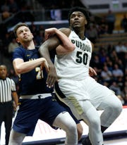 Trevion Williams of Purdue gets tangled with Cameron Wolter of Marian University as the Boilermakers shoot a free throw Thursday, November 1, 2018, at Mackey Arena. Purdue defeated Marian University 75-56.