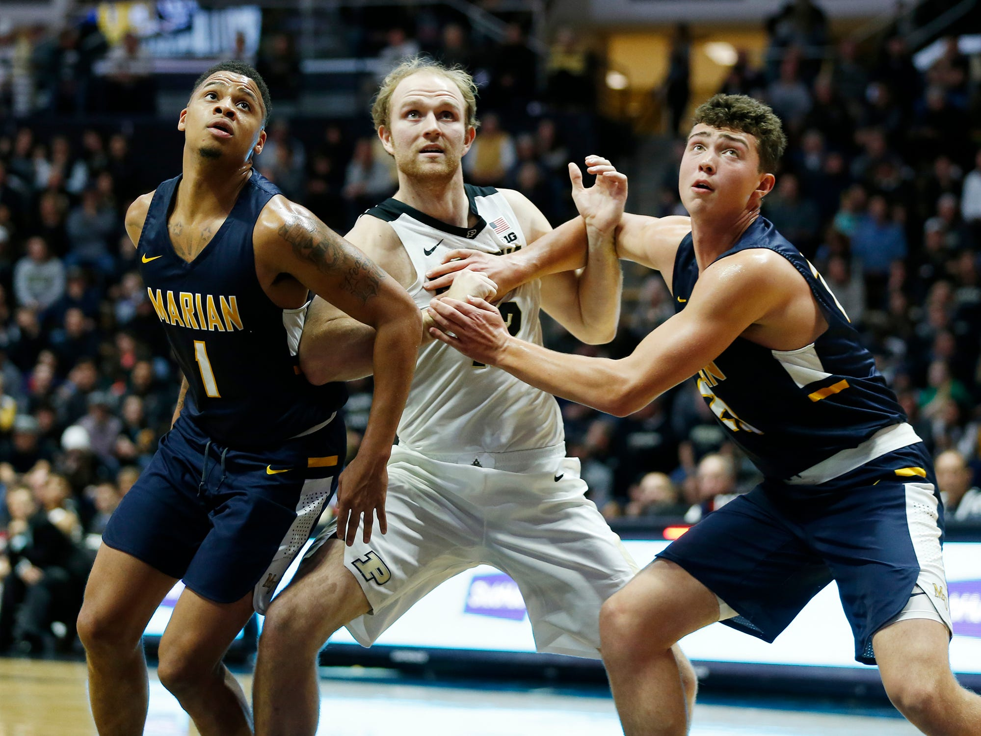 Evan Boudreaux gets sandwiched between TJ Henderson, left, and Luke Gohmann of Marian University during a Purdue free throw attempt in the first half Thursday, November 1, 2018, at Mackey Arena. Purdue defeat Marian University 75-56.