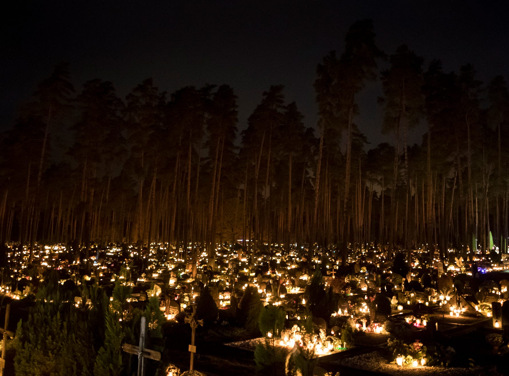 Relatives gather around some of the graves illuminated by candles during All Saints Day at the cemetery in Vilnius, Lithuania, Thursday, Nov. 1, 2018. Candles illuminated tombstones in graveyards across Europe as people communed with the souls of the dead on Thursday, observing one of the most sacred days in the Catholic calendar.(AP Photo/Mindaugas Kulbis)
