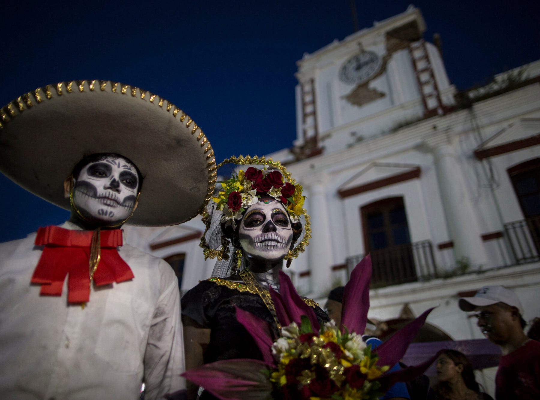 Performers in costume attend a Day of the Dead parade in Juchitan, Mexico, Wednesday, Oct. 31,  2018, the town where a caravan of thousands of Central American migrants are resting for a day as they make their way to the U.S. border. (AP Photo/Rodrigo Abd)
