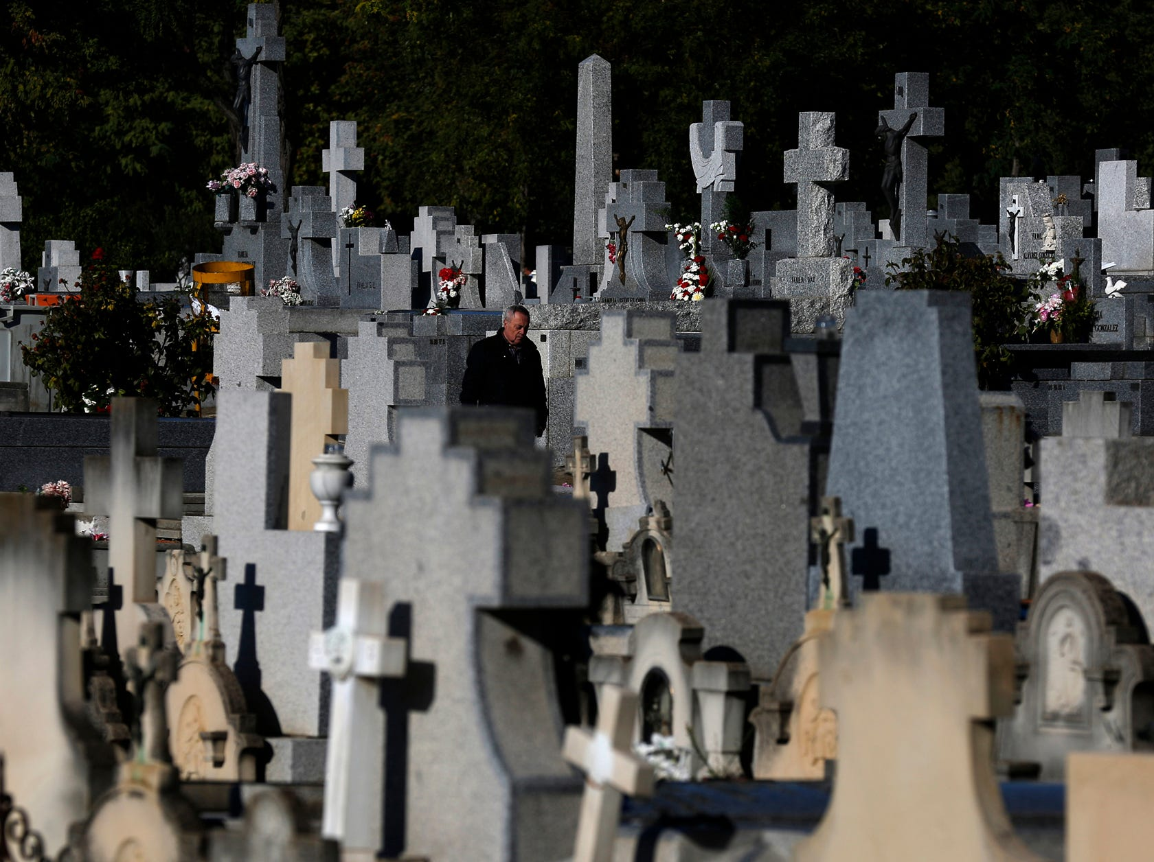 A man stands beside graves on All Saints Day, a Catholic holiday to reflect on the saints and deceased relatives, at the La Almudena cemetery in Madrid, Spain, Thursday, Nov. 1, 2018. (AP Photo/Manu Fernandez)