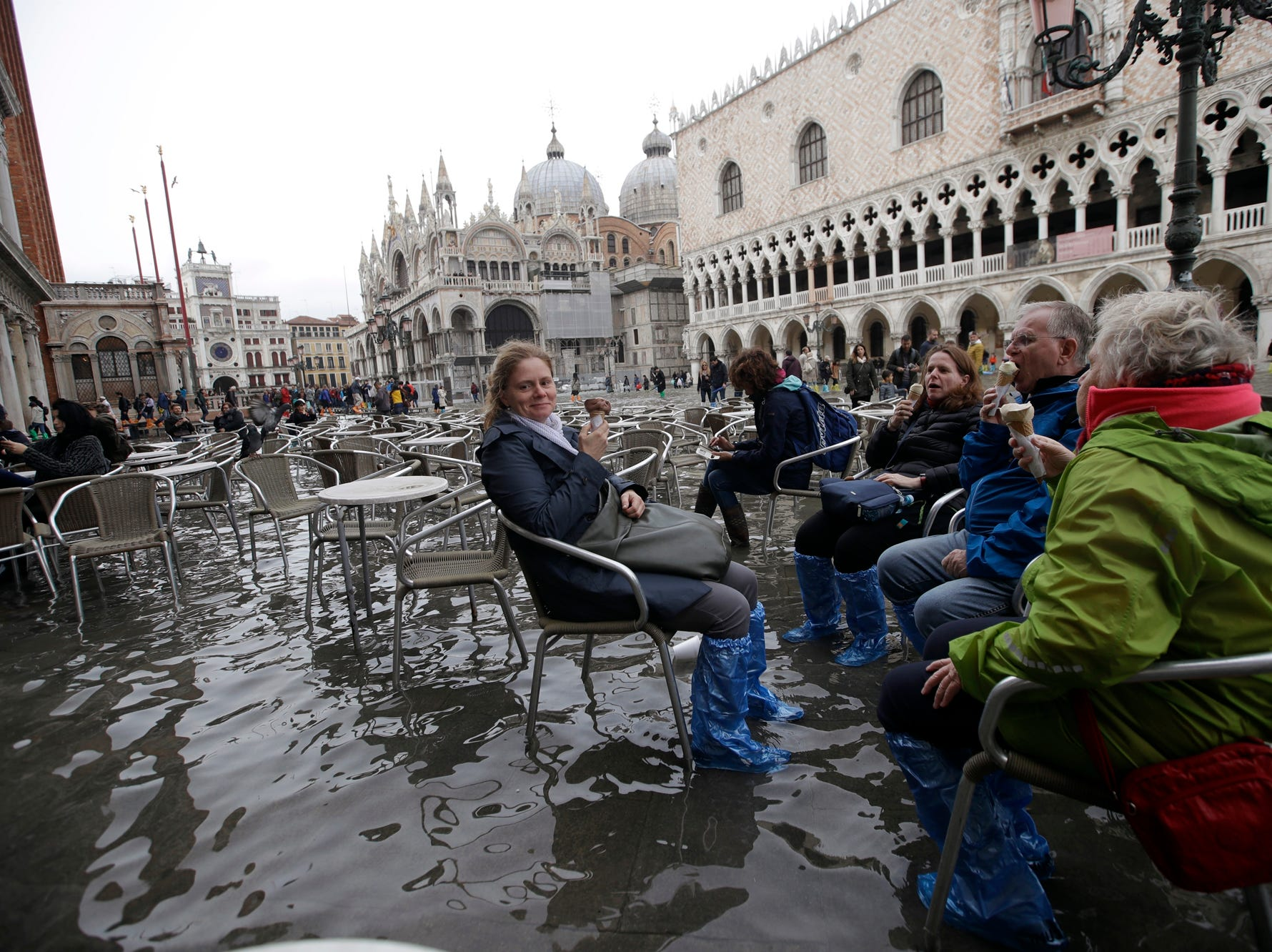 Tourists enjoy an ice-cream as they sit in flooded St. Mark's Square in Venice, Italy, Thursday, Nov. 1, 2018 as rainstorms and strong winds have been battering the country. Two people were killed when a falling tree crushed their car in the mountainous countryside in northwestern Italy, as rainstorms and strong winds continued to pummel much of the country. (AP Photo/Luca Bruno)