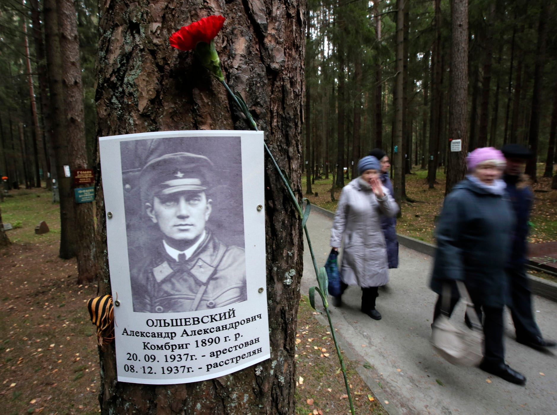 People walk past the portrait of Red Army commander Alexander Olshevsky arrested and shot in 1937 at Levashovo Memorial cemetery of victims of Soviet repressions during the Great Terror, the Soviet dictator Joseph Stalin's purges, on the outskirts of St.Petersburg, Russia, Tuesday, Oct. 30, 2018.  About 45,000 of the executed were buried in the Levashovo cemetery in 1937-1953, and October 30 is the Day of Remembrance for the Victims of Political Repressions in Russia. (AP Photo/Dmitri Lovetsky)