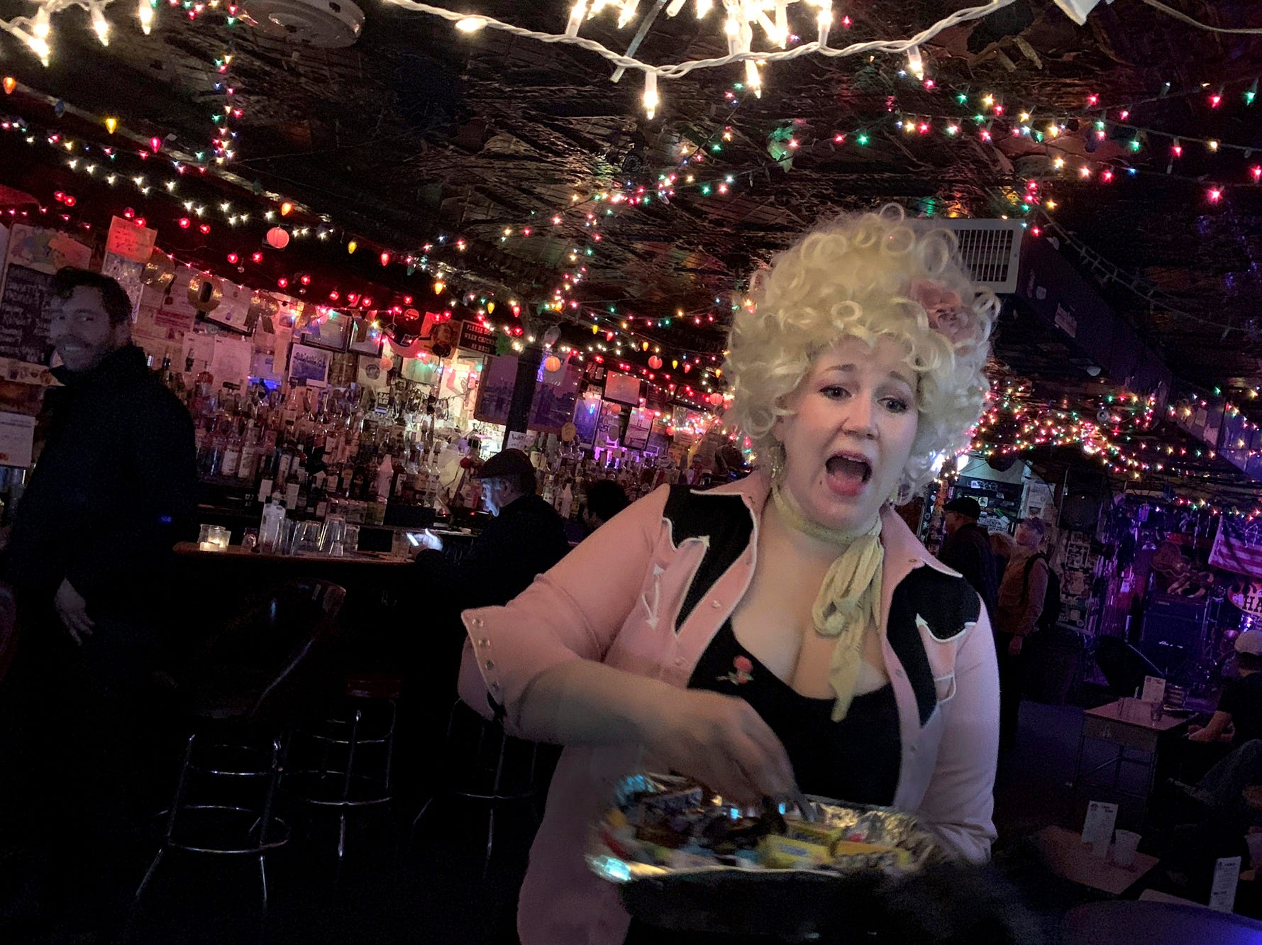 A hostess at a local bar in Brooklyn hands out candy to trick or treaters on Halloween in New York on Wednesday Oct. 31, 2018. (AP Photo/Wong Maye-E)