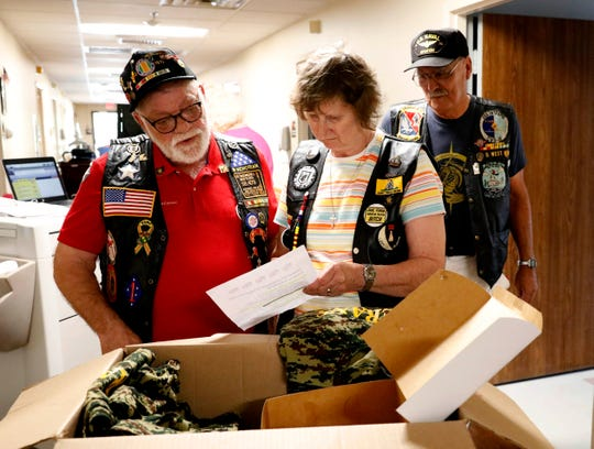 Tom Estes, left, Carol West, center, and Don West check a list of a veterans at Logan Care and Rehabilitation Center Tuesday, Oct. 9, 2018, in Logan. Estes and Don West are Vietnam veterans and visit other veterans at the nursing home once a month.