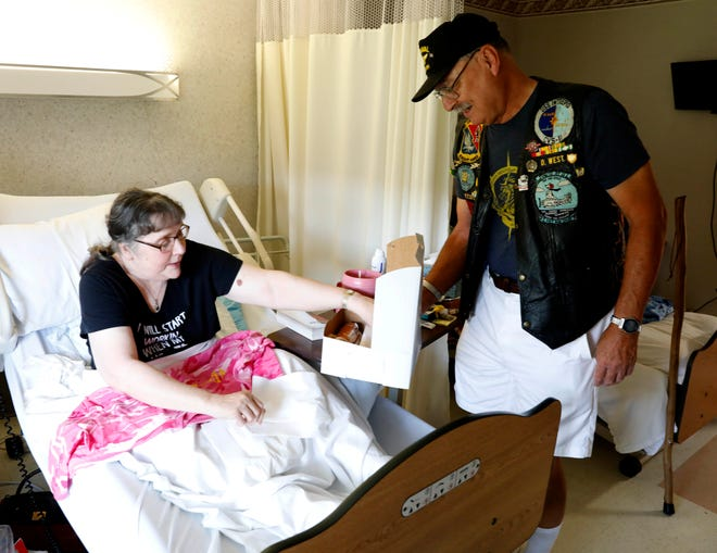 Don West, right, holds a box as Patty Fry gets one of the doughnuts West and fellow Vietnam veteran Tom Estes brought to their fellow veterans at the nursing home Tuesday, Oct. 16, 2018, at Logan Care and Rehabilitation Center in Logan. West and Estes visit the veterans who live at the nursing home once a month.