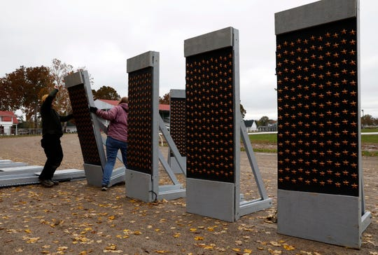 Mark Bateson, left, and Sharon Flowers set up a replica of the National World War II Memorial Friday, Nov. 2, 2018, at the Fairfield County Fairgrounds in Lancaster.