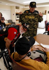 Tom Estes, left, and Don West, talk to Logan Care and Rehabilitation resident Marcellas Truxal Tuesday afternoon, Oct. 9, 2018, in Logan. Estes and West, Vietnam veterans, visit other veterans at the nursing home once a month. In October they brought veterans t-shirts to the residents to wear for their November visit to mark Veterans Day.