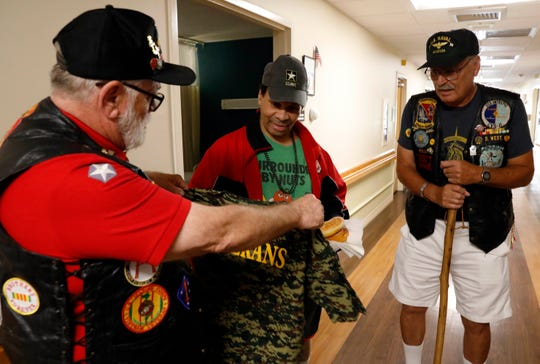 Tom Estes, left, and Don West give Howard Butler a veterans t-shirt Tuesday, Oct. 9, 2018, at Logan Care and Rehabilitation Center in Logan. Estes and West, Vietnam veterans, visit fellow veterans at the nursing home once a month.