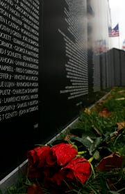 Roses lay on the grass in front of a replica of the Vietnam Veterans Memorial Wall Friday, Nov. 2, 2018, at the annual Freedom's Never Free event at the Fairfield County Fairgrounds in Lancaster.