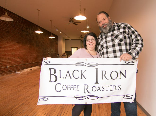 Having recently taken a lease at 119 W. Grand River Ave. in downtown Howell, Black Iron Coffee Roasters owner Kevin Ridge and his wife Darcie hold a temporary sign Friday, Nov. 2, 2018 in the coffee shop which opened in April of this year.
