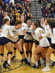 South Lyon players celebrate their victory over Brighton in the district volleyball championship match on Thursday, Nov. 1, 2018.