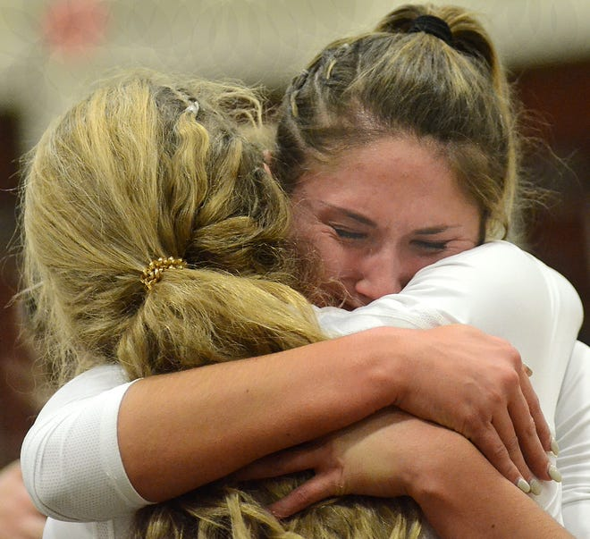 Brighton's Alexa Bowles (facing camera) hugs teammate Ashley Brown after a loss to South Lyon in the district volleyball championship match on Thursday, Nov. 1, 2018.