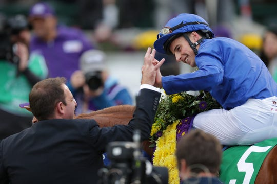 Jockey William Buck is congratulated after his mount, Line of Duty, was declared the winner of the Breeders' Cup Juvenile Turf following a foul claim against the horse and rider. Nov. 2, 2018