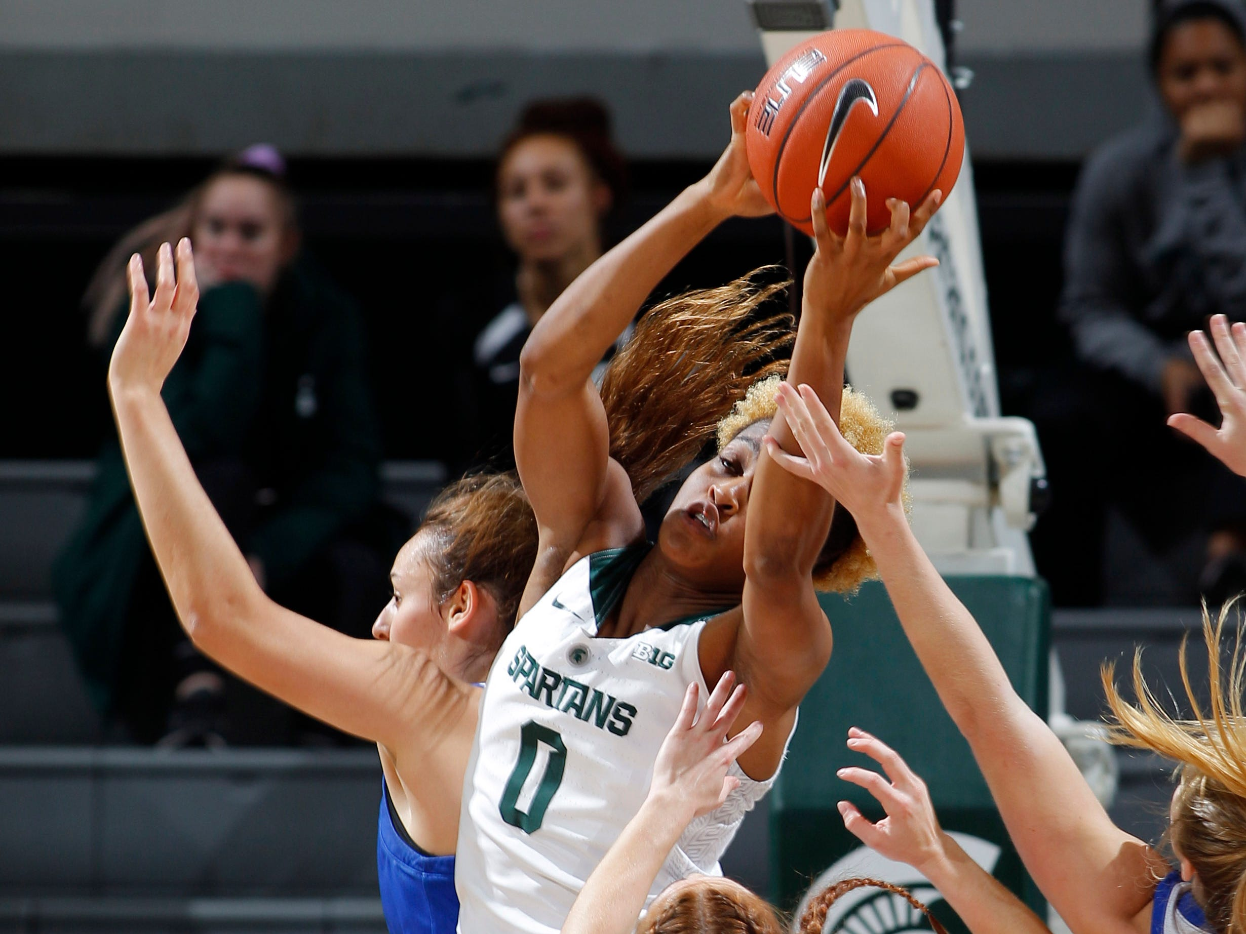 Michigan State's Shay Colley (0) grabs a rebound over Taryn McCutcheon (4) and Hillsdale's Hunter Stevens, left,, Thursday, Nov. 1, 2018, in East Lansing, Mich.
