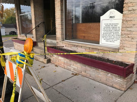 Caution tape surrounds the century-old building at 105 N. Bridge St. on Tuesday, Oct. 30, 2018 after a portion of the brick wall on the exterior collapsed. The former home of JB's Party Store in Dimondallea has new owners with plans to rehab the building and open a new restaurant.