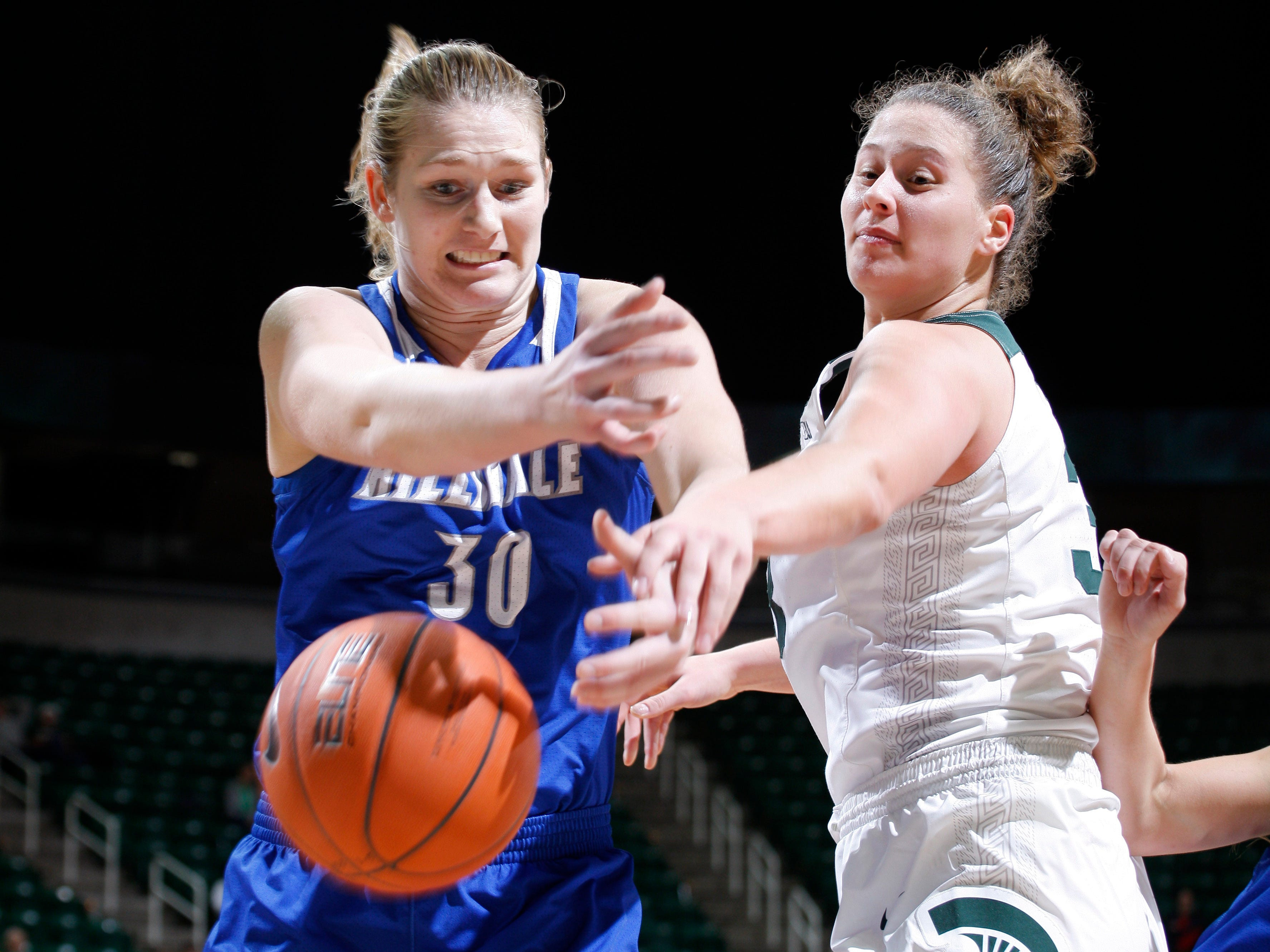Michigan State's Jenna Allen, right, and Hillsdale's Julia Wacker reach for a loose ball, Thursday, Nov. 1, 2018, in East Lansing, Mich.