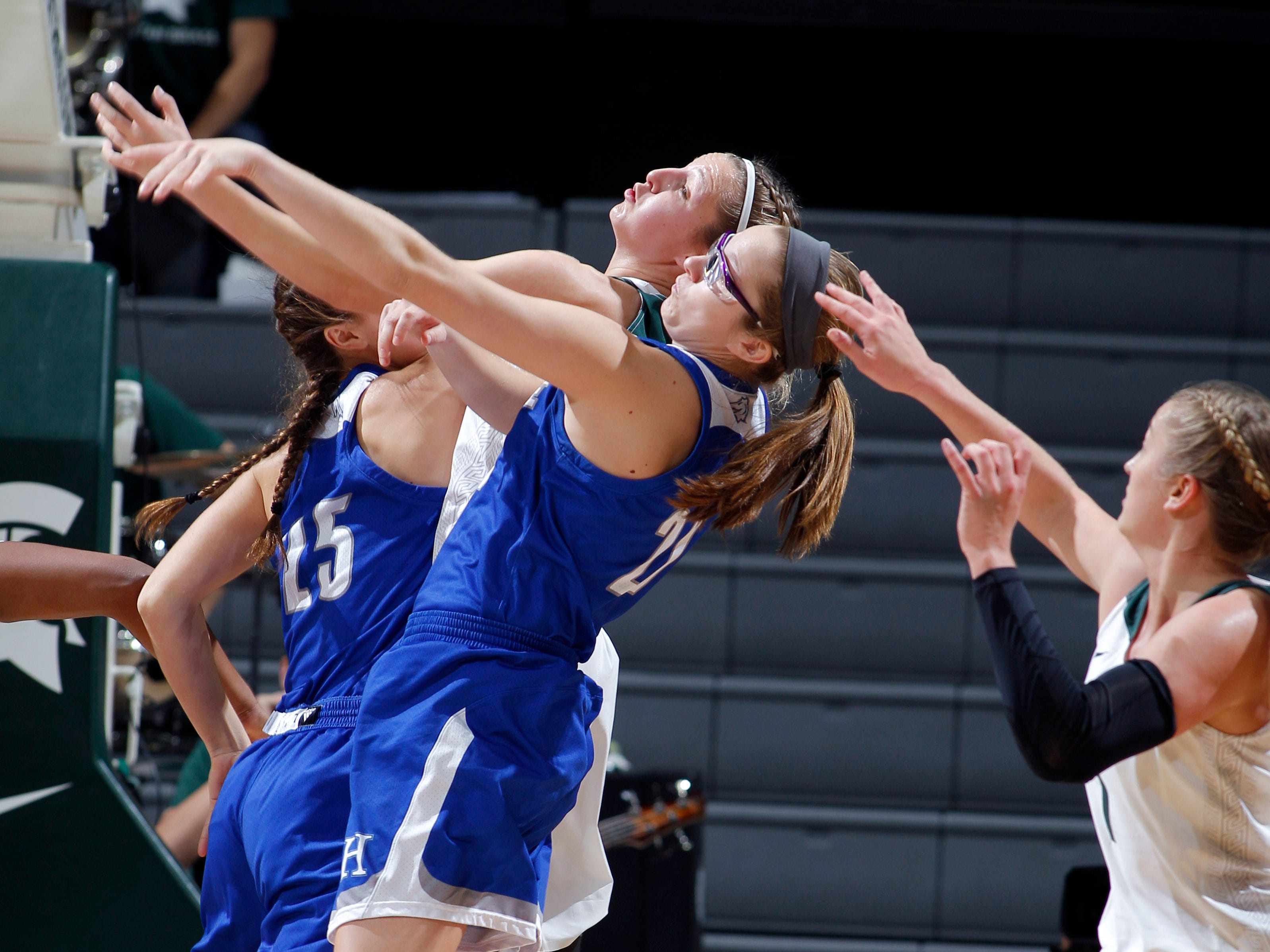 Michigan State's Claire Hendrick, center, and Tory Ozment, right, and Hillsdale's Sydney Anderson (25) and Lauren Daffenberg (21) battle for a rebound, Thursday, Nov. 1, 2018, in East Lansing, Mich.