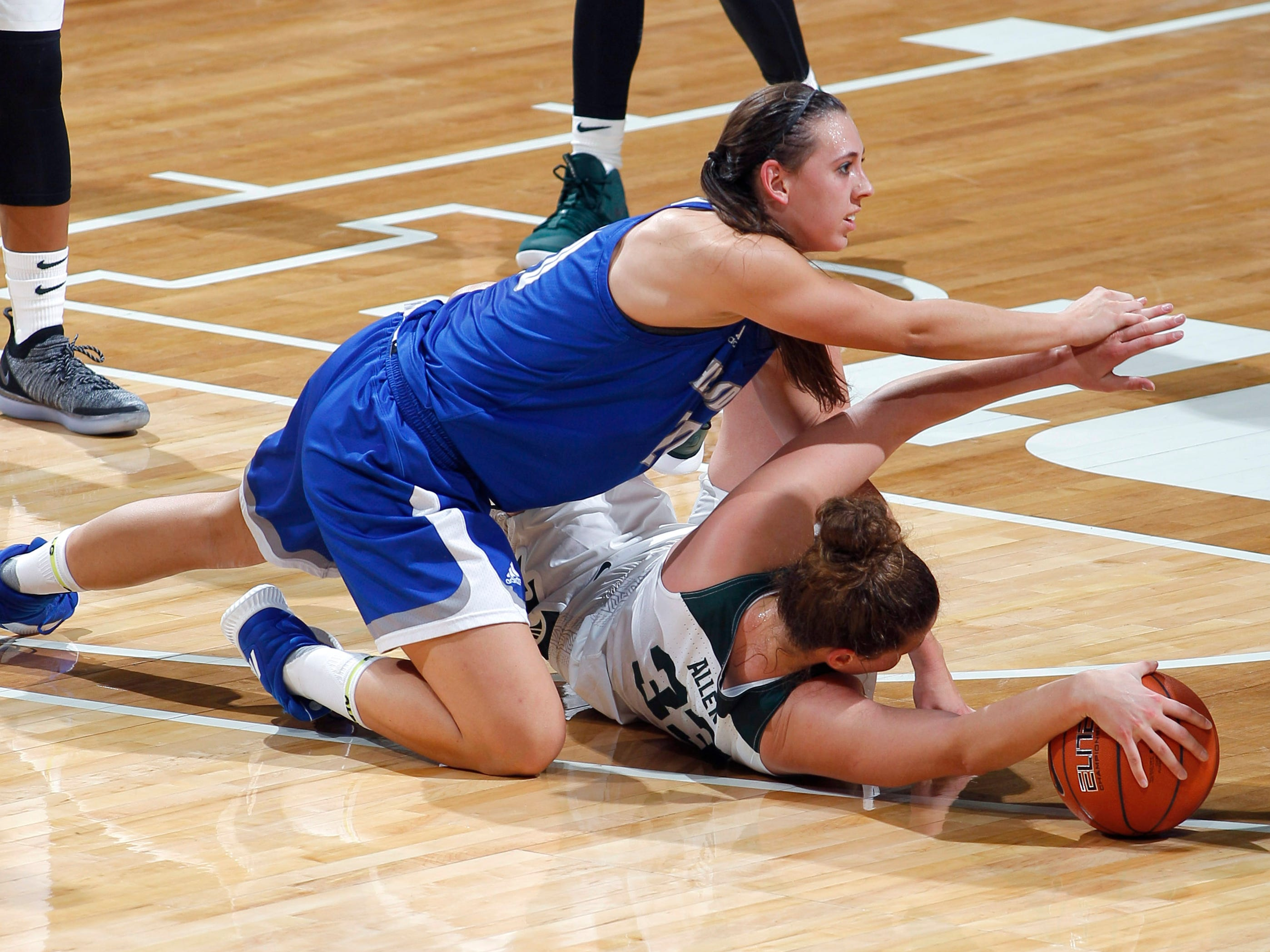 Hillsdale's Makenna Ott, top, and Michigan State's Jenna Allen wrestle for the ball, Thursday, Nov. 1, 2018, in East Lansing, Mich.