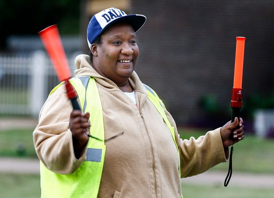 Ross Elementary parent Danielle Jones directs after school traffic Friday afternoon.