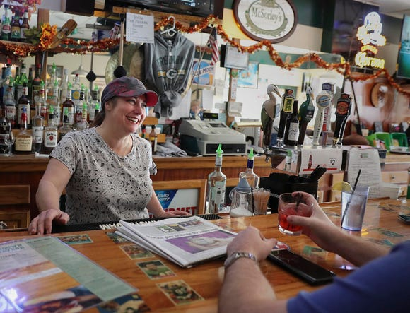 "Kari Walker, co-owner of Touchdown Tavern in Reedsburg, chats with a patron last year. She says, ""We don't watch the news here"" because politics is too touchy. ""We watch sports ... on some level, that's safe."""