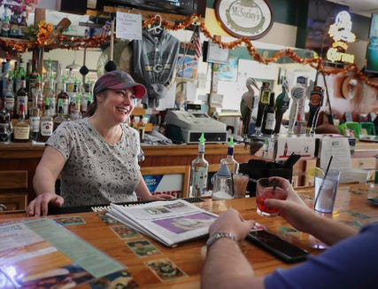 """Kari Walker, co-owner of Touchdown Tavern in Reedsburg, chats with a patron last year. She says, """"We don't watch the news here"""" because politics is too touchy. """"We watch sports ... on some level, that's safe."""""""