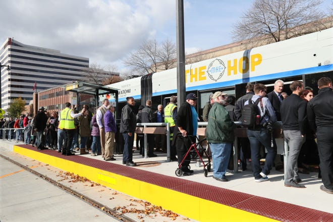 People wait to board The Hop streetcar  at the Cathedral Square Park stop.