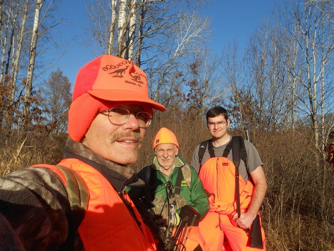 Randall Schwalbach, left, of Appleton takes a photo while deer hunting with his father Ralph of West Allis, and Randall's nephew, Joseph, of Wauwatosa.