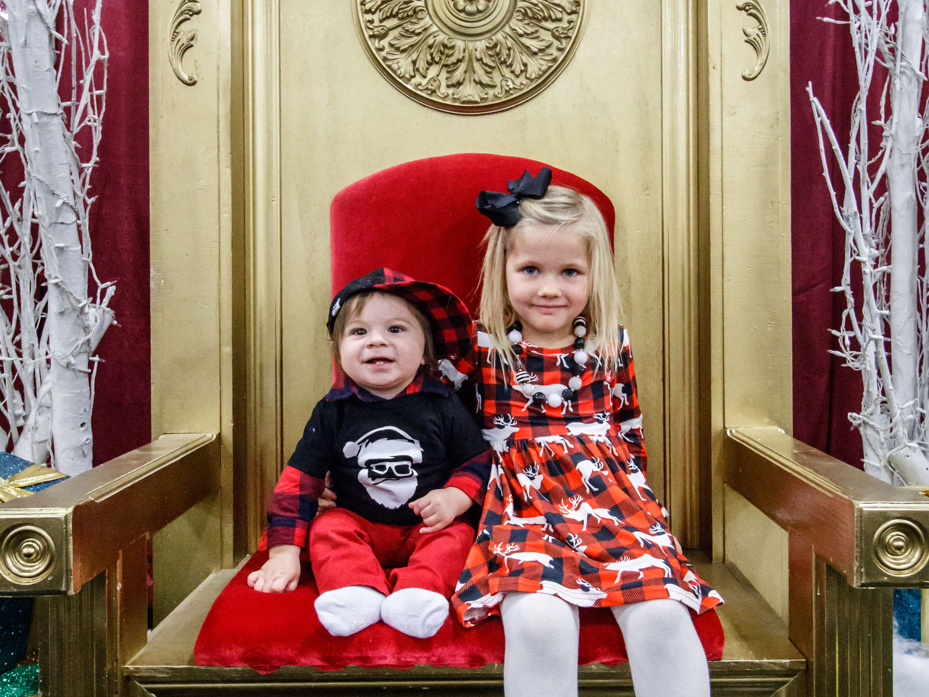 Nine-month-old Moses Zetina of Oconomowoc and Delanie Pfeiffer, 5, of Hartland, check out Santa's golden chair during the Milwaukee Holiday Boutique at Wisconsin State Fair Park on Friday, Nov. 2, 2018. The event features over 200 vendors, pictures with Santa, live entertainment and much more.