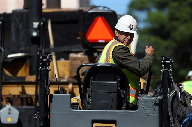 A construction worker operates a steam roller while paving a road last month in California.  The federal government said the U.S. economy created 250,000 new jobs in October.