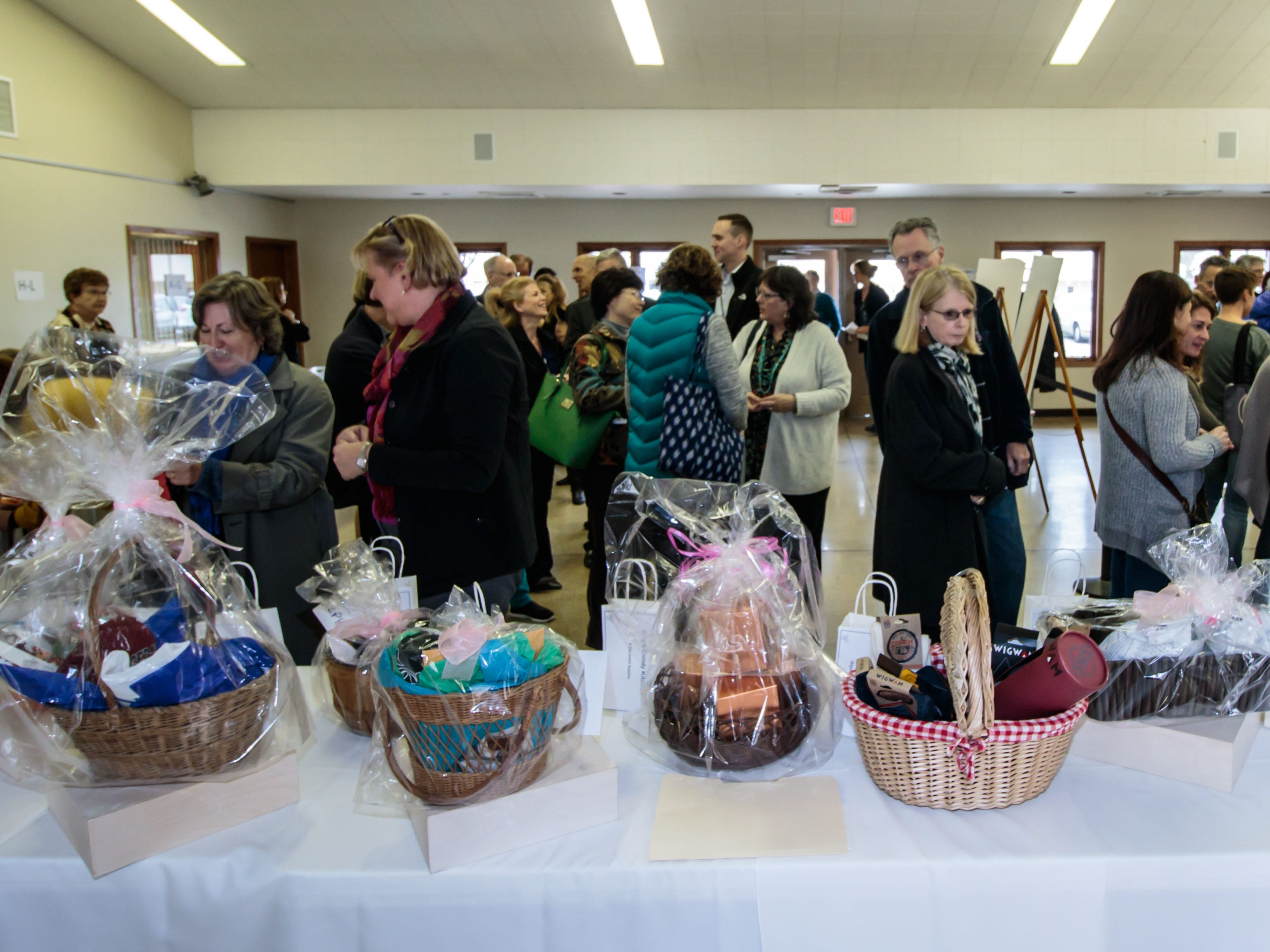 Attendees look over a variety of raffle items during the Empty Bowls fundraising event at the Ozaukee Pavilion in Cedarburg on Thursday, Nov. 1, 2018. Proceeds from the event will benefit Family Sharing's food pantry and provide 600 Ozaukee County families with Thanksgiving dinners.