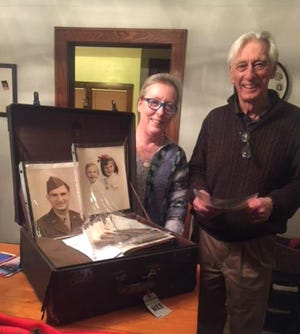 Darla Thompson-Webb presents a suitcase to Mike Sokolowski containing letters, photos and other items belonging to his parents, who both died before he was 6 years old. Thompson-Webb's grandson found the suitcase in the attic of a house he bought in South Milwaukee and then she tracked down the owner's family.