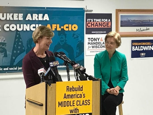 Democratic U.S. Sen. Tammy Baldwin speaks Friday afternoon at Milwaukee Area Labor Council while U.S. Sen. Elizabeth Warren of Massachusetts looks on.