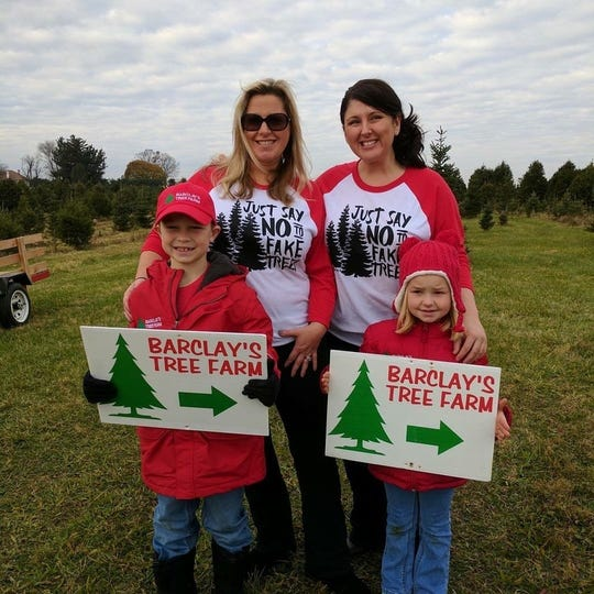 Samantha Barclay (left), her sister-in-law Holly Barclay, with Holly's children Ryan and Lauren, at Barclay's Tree Farm in Cranbury.