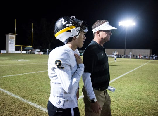 Autauga quarterback Tripp Carr (2) talks with his head coach and dad, Bobby Carr on the sideline as they take on Patrician at Autauga Academy on Thursday, Nov. 1, 2018. Autauga defeated Patrician 42-0.