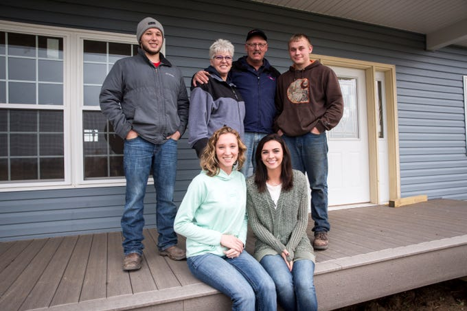 Brandon Dailey, Stacie Walter, Allen Walter, Carson Hartzell, Emilie Dailey and Sara Walter stand in front of the Walter's rebuilt home along North 500 West near Portland a year after the house was destroyed during a tornado.