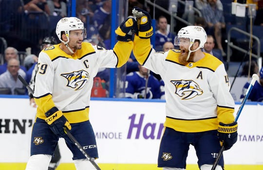 Nashville Predators defenseman Roman Josi (59) celebrates his goal against the Tampa Bay Lightning with defenseman Ryan Ellis (4) during the first period of an NHL hockey game Thursday,.