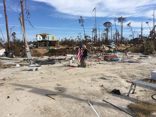 Marsha Borgeson holds an American flag, standing on what used to be the living room of her home in Mexico Beach that was destroyed by Hurricane Michael.