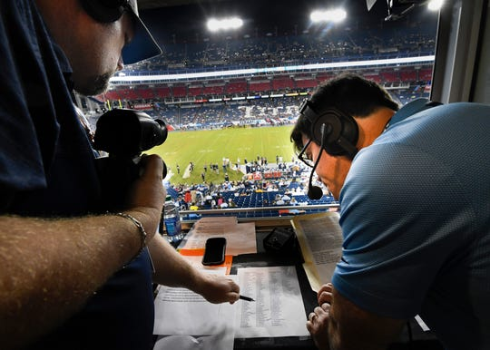 Titans Radio game day host Rhett Bryan points out a player on the roster for Mike Keith during their radio broadcast of the Titans game against the Vikings Nissan Stadium Thursday, Aug. 30, 2018, in Nashville, Tenn.