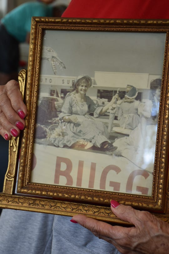 Dolly Scott, 83, holds a photo of her as 1966's Swamp Buggy Queen. In honor of past queens, Scott attended Saturday's Swamp Buggy Parade, which kicked off the 70th racing season.