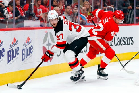 New Jersey Devils center Pavel Zacha (37) is defended by Detroit Red Wings right wing Martin Frk (42) in the first period at Little Caesars Arena.