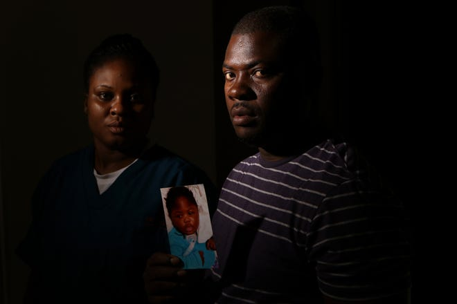 Ocroimy Dolcin and his wife, Modeline Auguste, pose with a photo of their daughter, Dorcase Dolcin, who was one of at least ten children who died at the Wanaque Center for Nursing and Rehabilitation from an adenovirus outbreak.