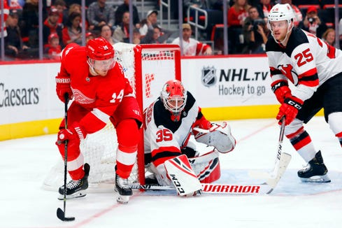 Detroit Red Wings right wing Gustav Nyquist (14) skates with the puck around net and defenseman Mirco Mueller (25) in the second period at Little Caesars Arena.