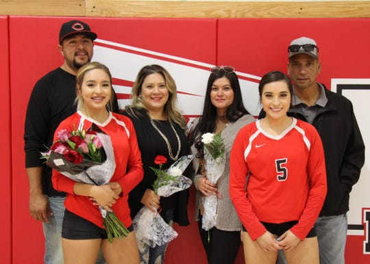 Chassity Onsurez (4) and Anyssa Rodriguez (5) pose with their families after Thursday's match against Eunice. Loving won in four sets.