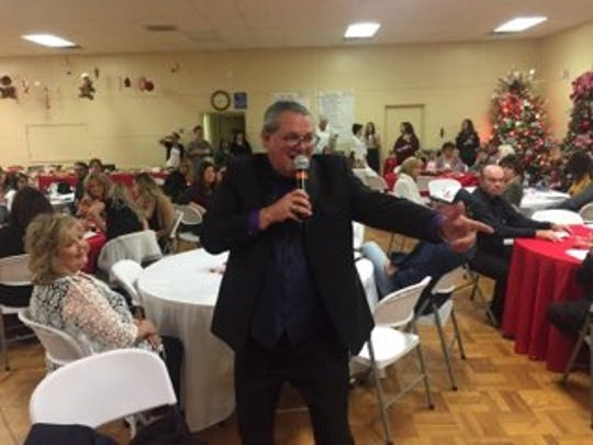 Auctioneer Dave Rogers points to a bidder during Thursday night's Assistance League of Carlsbad Christmas Tree Auction.