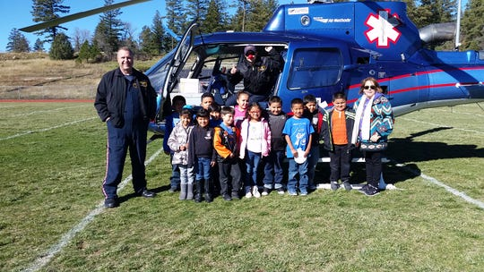 Students in Rose Helmke's first grade class at Mescalero Schools pose with Emergency Medical technicians Russ Buttars and Steph Bunker.