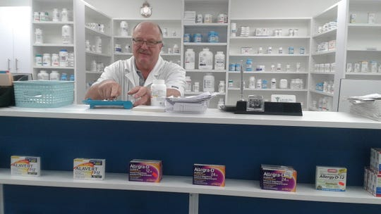 Pharmacist Michael Plotkowski counts out pills at Lincoln Rx Pharmacy. The store is participating in a new telehealth program.