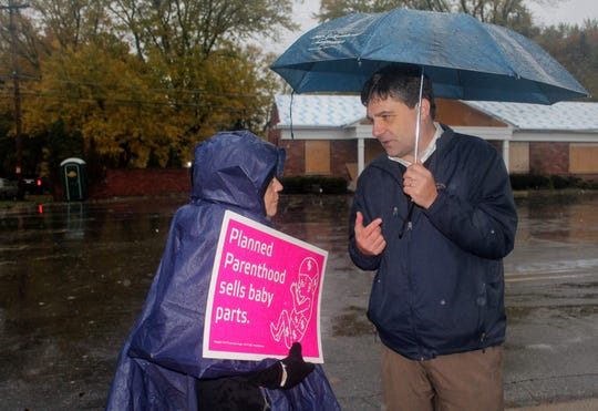 State Sen. Patrick Colbeck, R-Canton, speaks to Lynn Mills, the director of Pro-Life Michigan, outside a building they say is expected to become a Planned Parenthood facility in Livonia.