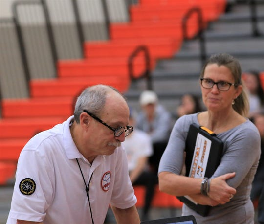 Northville coach Julie Fisette (right) tries to get a clarification from the MHSAA official in Thursday's Division 1-District 20 volleyball final.